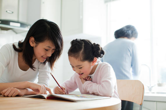 Girl doing her homework at the kitchen table while her mother helps.