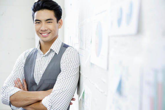Portrait of young man in office next to wall presentation